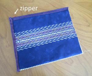 The tube lies flat on the table, with the zipper along the top edge.